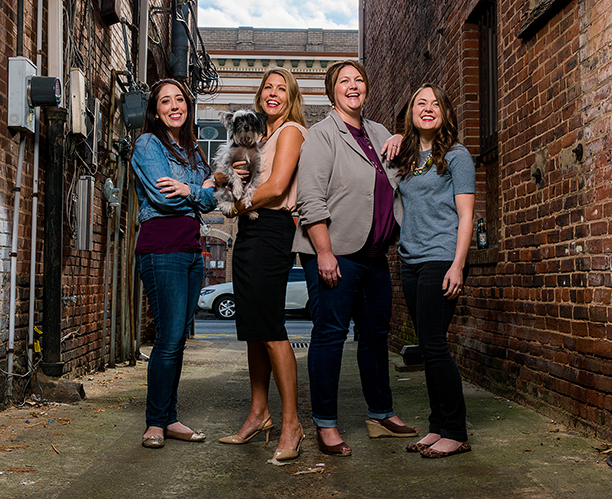 A group of 4 - Ashley, Kriston, Julie and Emily and the pup (Saki) stand in the alley in an area called Marietta Square (Downtown Marietta, Georgia) Northwest of Atlanta.